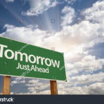 stock-photo-tomorrow-green-road-sign-against-dramatic-sky-clouds-and-sunburst-84325612
